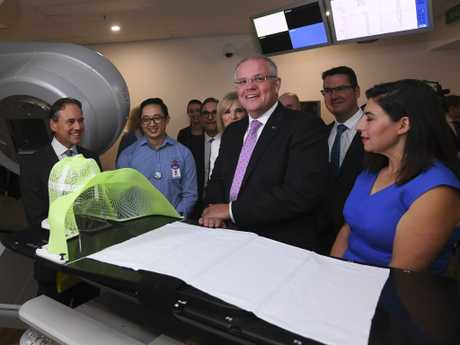 Prime Minister Scott Morrison (centre) inspects a radiation machine during a visit to Icon Cancer Centre in Canberra with Health Minister Greg Hunt (left) yesterday. Picture: Lukas Coch/AAP
