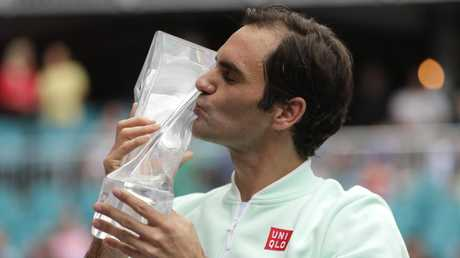 Roger Federer, of Switzerland, kisses the trophy after defeating John Isner
