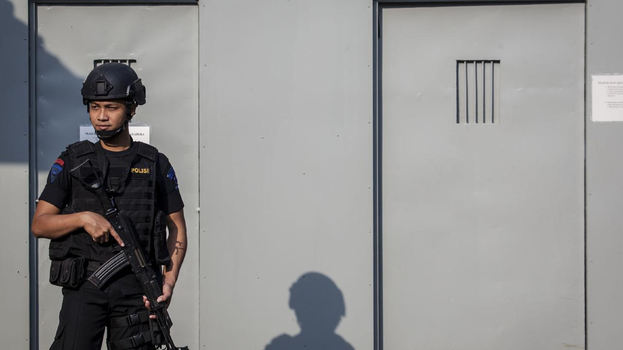 A Indonesian policeman standing guard at the entrance gate to 'execution island' where prisoners convicted on drugs charges are killed. Picture: Ulet Ifansasti/Getty Images