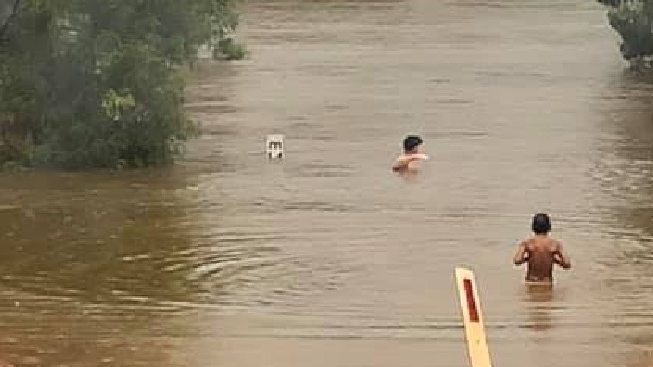 Swimmers dice with death at a flooded crossing in Arnhem Land on Tuesday. Picture: Supplied