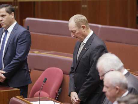 Australian senator Fraser Anning, center, bows his head in the chamber at the start of the senate session yesterday. Picture: AP