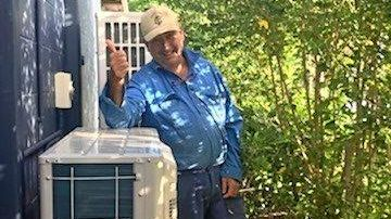 Bloomsbury resident Frank Clayton next to his split system air conditioner he said was destroyed when an outage occurred in the Ergon Energy network in February.