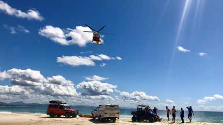 Westpac Life Saver Rescue Helicopter prepares to winch a patient who was pulled from the ocean unconscious at Clarkes Beach at Byron.