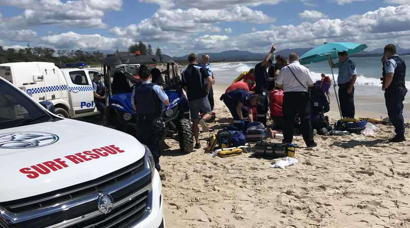 Emergency services work to stabilise a woman who was pulled unconcious from the water at Clarkes Beach, Byron Bay.