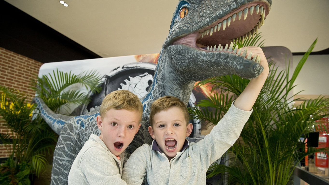 Lars (left) and Claude Archer check out a velociraptor dinosaur on display as part of Jurassic World for school holiday activities at Grand Central, Friday, April 5, 2019.