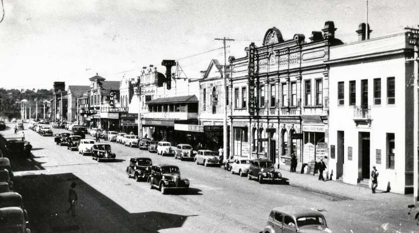 PAST: Margaret St in 1946-50, looking east from the intersection with Ruthven St, with cars parked in the centre and on both sides of the street. Businesses include National Mutual, Tattersall's Hotel, John Cay and Co Auctioneers and CMA, heading down to the post office and court house.
