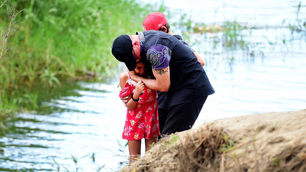 Barak Austral Snr, father of Barak Austral who drowned with his brother Jhulio Sariago, embraces daughter Chasey at the Ross River. Picture: Alix Sweeney.