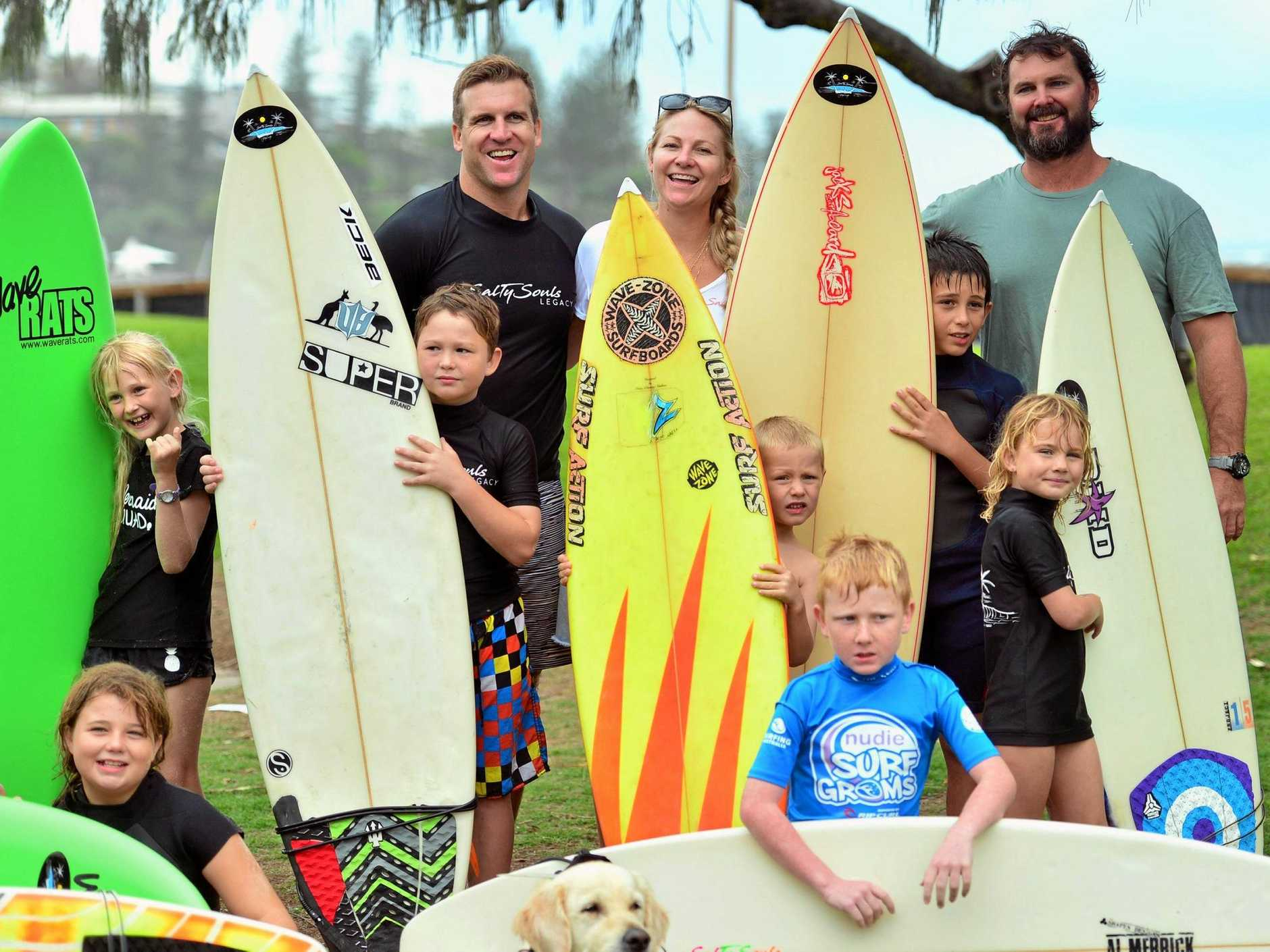 STOKED: (From left) Kerry and Tamara Smith, and Michael Kennedy with some of the children a part of the Salty Souls Legacy program helping vulnerable learn to surf and enjoy the water.