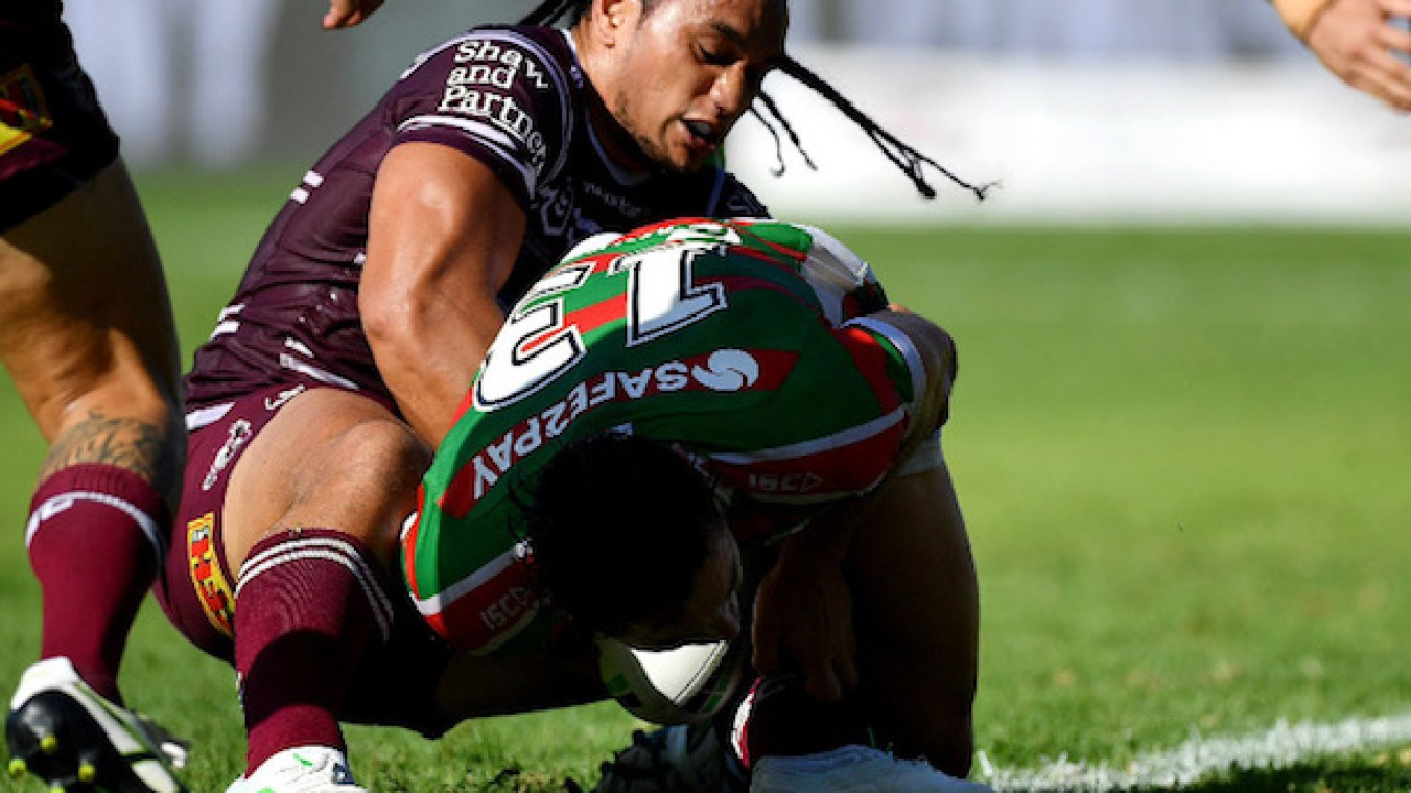 Manly prop Marty Taupau holds up South Sydney's Cameron Murray to save a certain try.