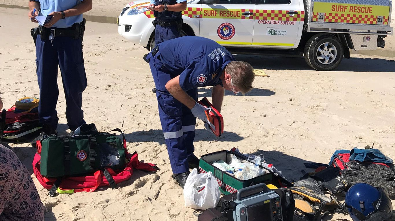 Emergency services treat a man who was unresponsive when he was pulled from the water at Clarkes Beach, Byron Bay.