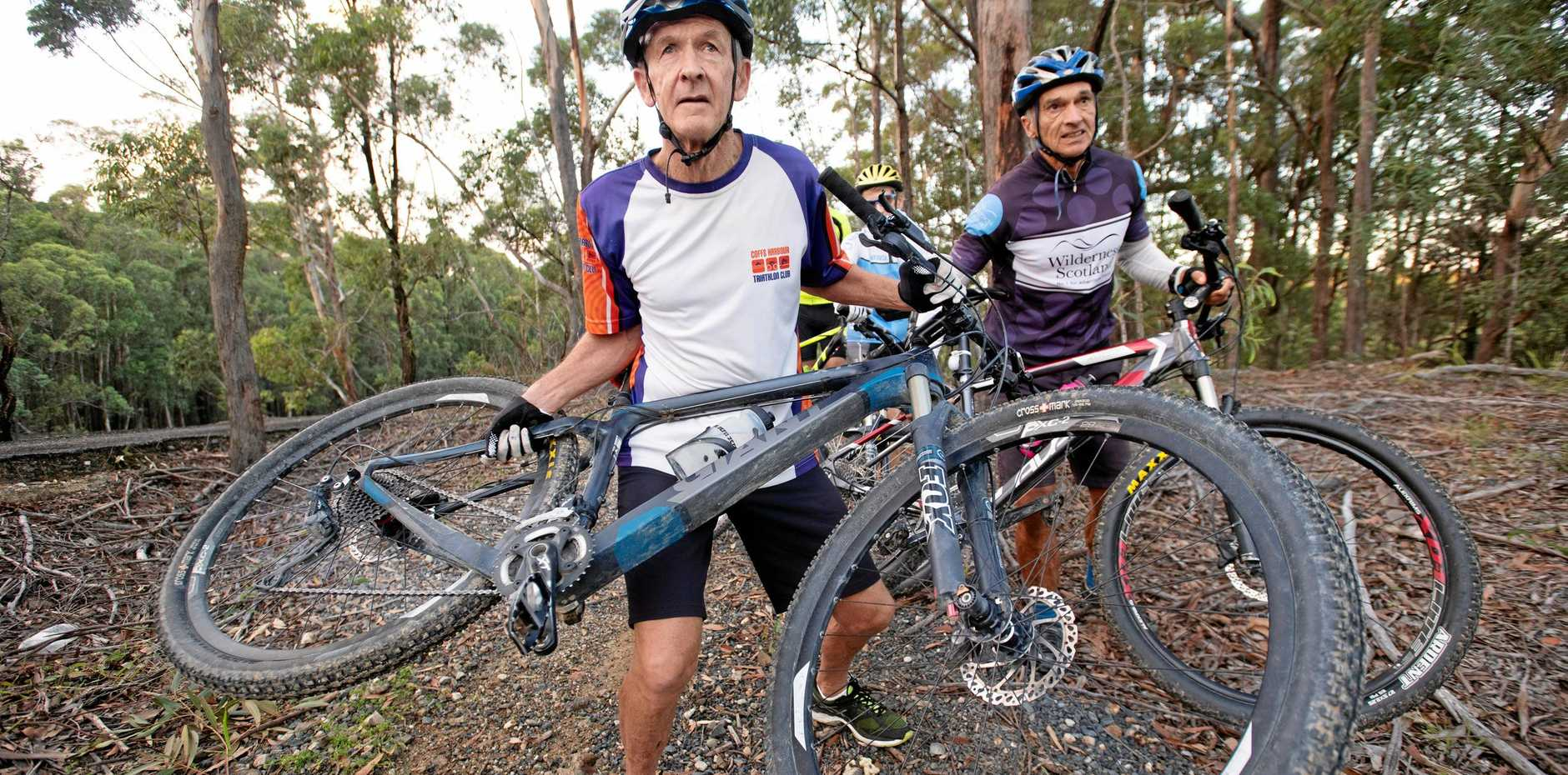 SCARY: Mountain bike riders set upon by dogs, Rod Wilbers front and behind Dave Moffatt show how they held up their bikes for protection.