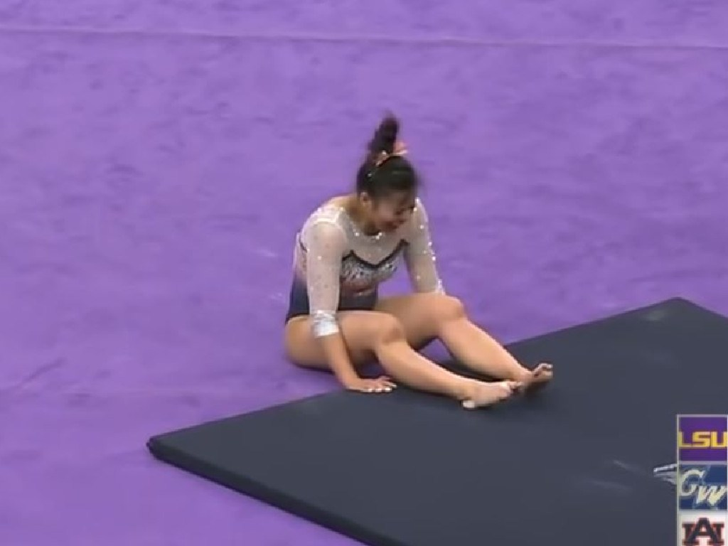 The gymnast writhes in pain.