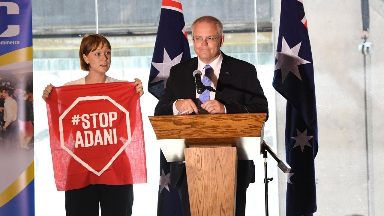 A Stop Adani protester takes to the stage where Australian Prime Minister Scott Morrison was making a speech at the Valley Chamber of Commerce business luncheon in Brisbane. Picture: AAP/Dave Hunt