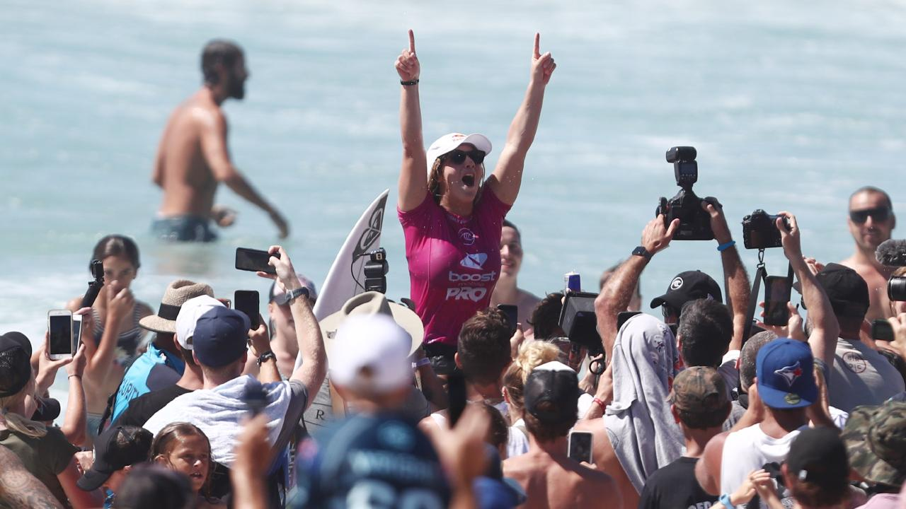 Teenager Caroline Marks is chaired along the beach. Picture: Getty