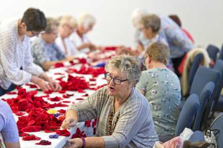 U3A members including Annette ODea work on the poppy-themed community art installation for Anzac Day, Wednesday, April 10, 2019.