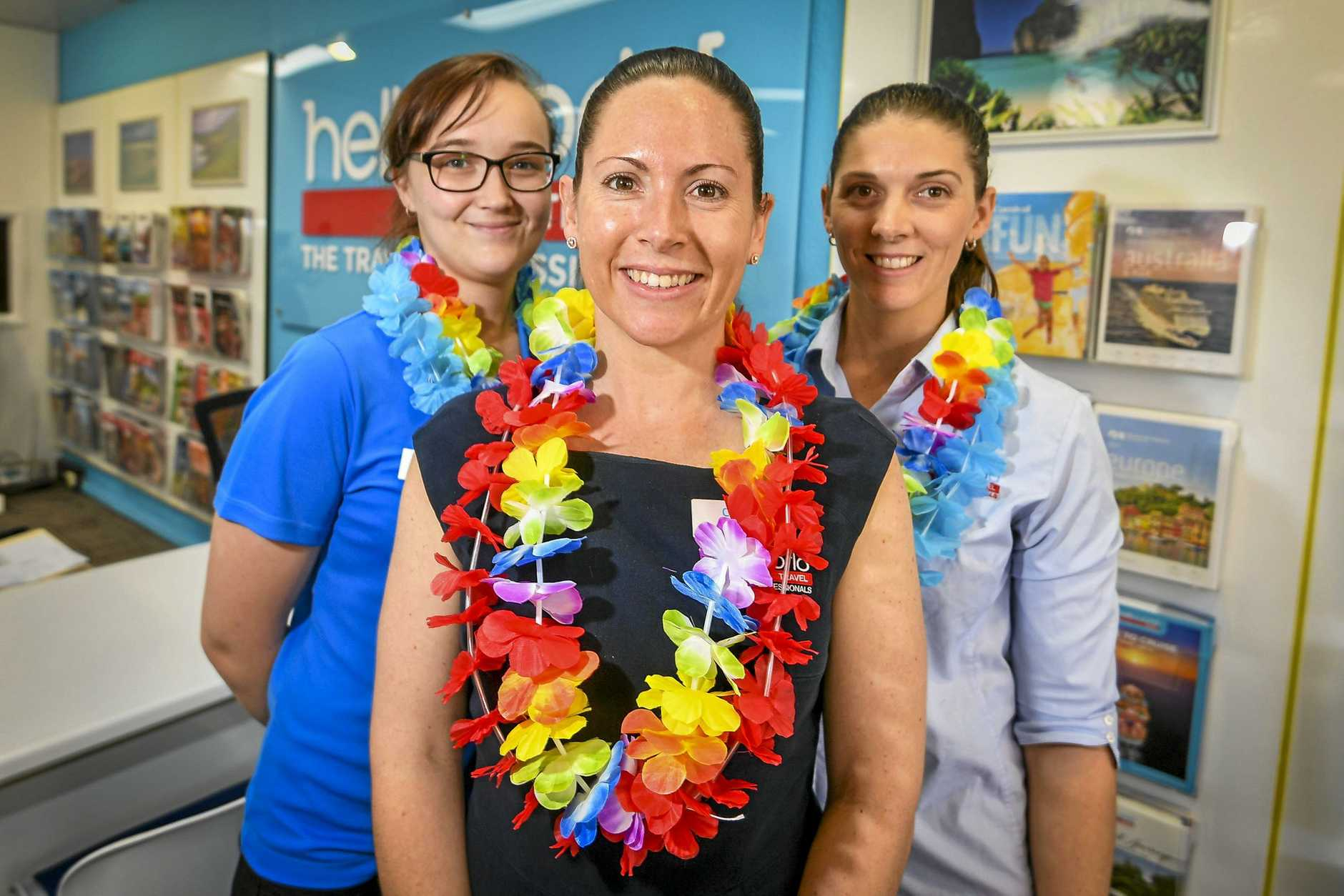 Carmen Ward, Jessica Driessen and Amelia Robinson are dressing up Helloworld Travel on Gladstone's Goondoon Street as part of Harbour Festival's Tropical Wednesday event.