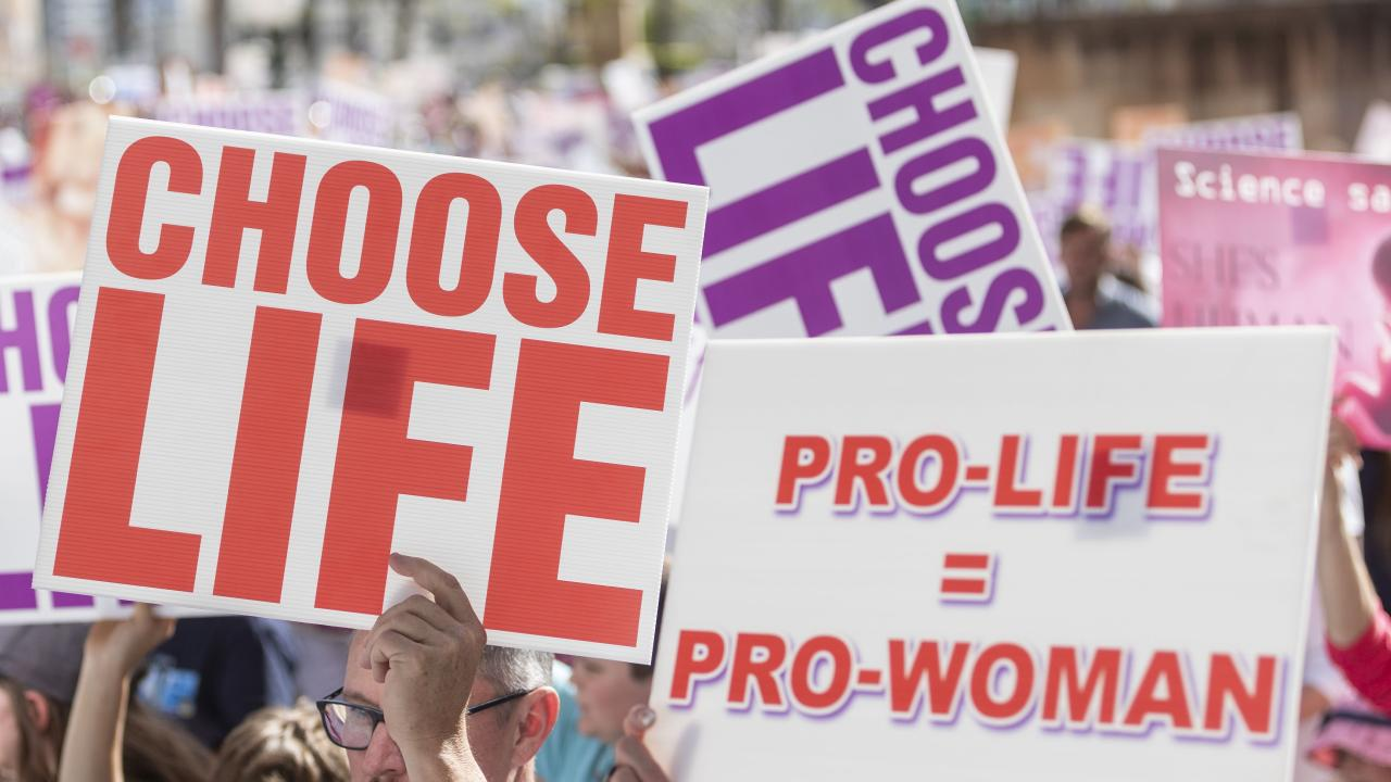 Protesters hold placards during a pro-life rally in Brisbane last year. File picture