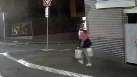 He was filmed walking towards the building carrying two large drums.