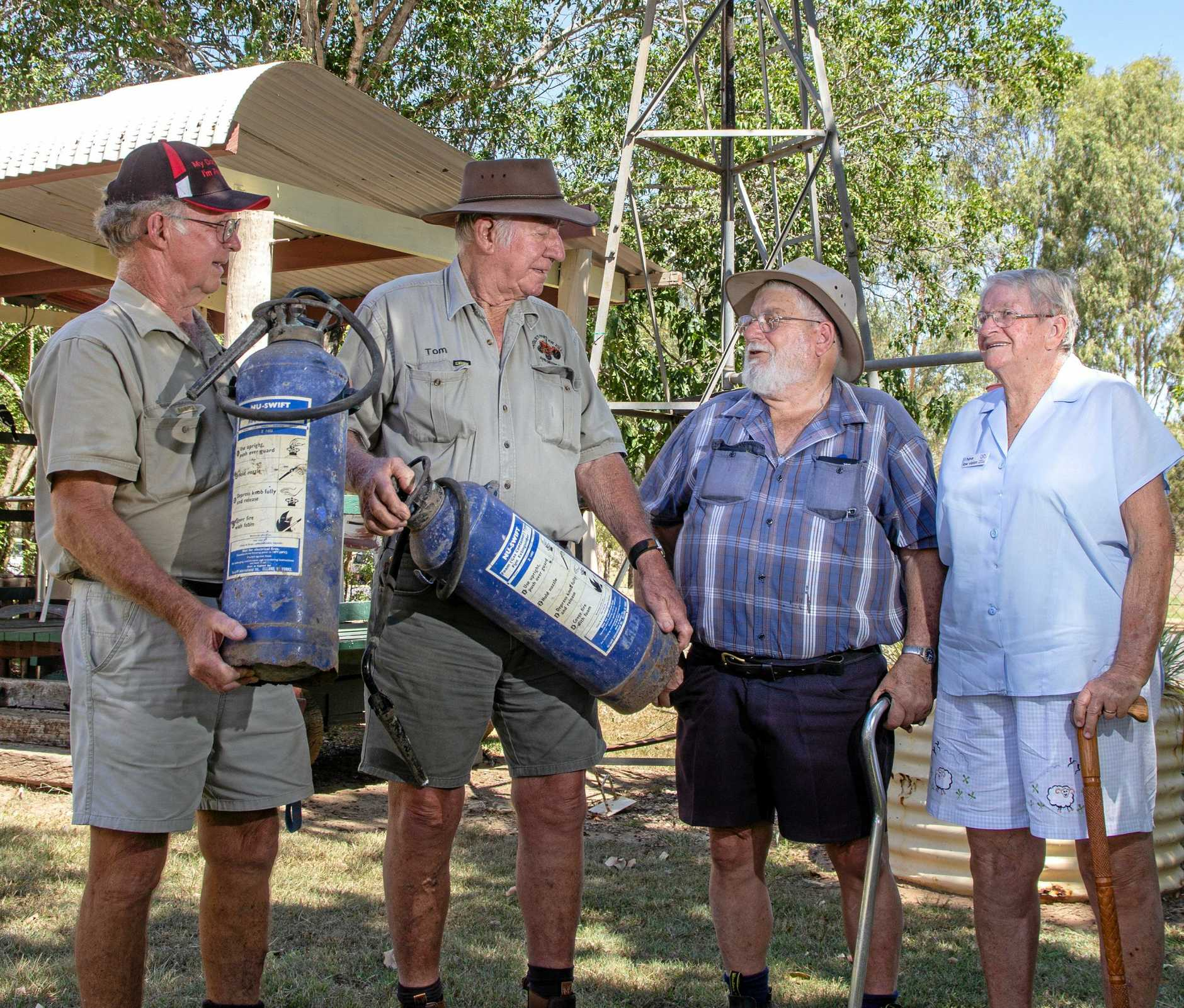 HEARTWARMING GESTURE: Laidley Pioneer Village's John Barwell and Tom Mulcahy hold the fire extinguishers Bob and Gloria Sanderson donated to the village to replace a similar extinguisher stolen last year.
