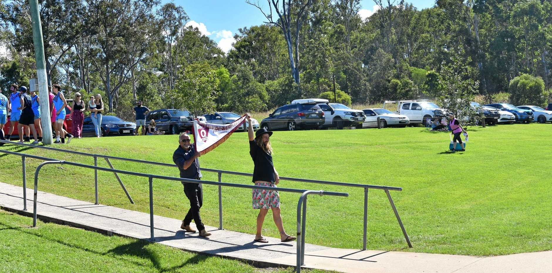 Gympie Cats life member Ray Warren and Cats midfielder Lanze Magin unveil the 2018 Wide Bay Premiership Flag to the supporters at their first home game of 2019.
