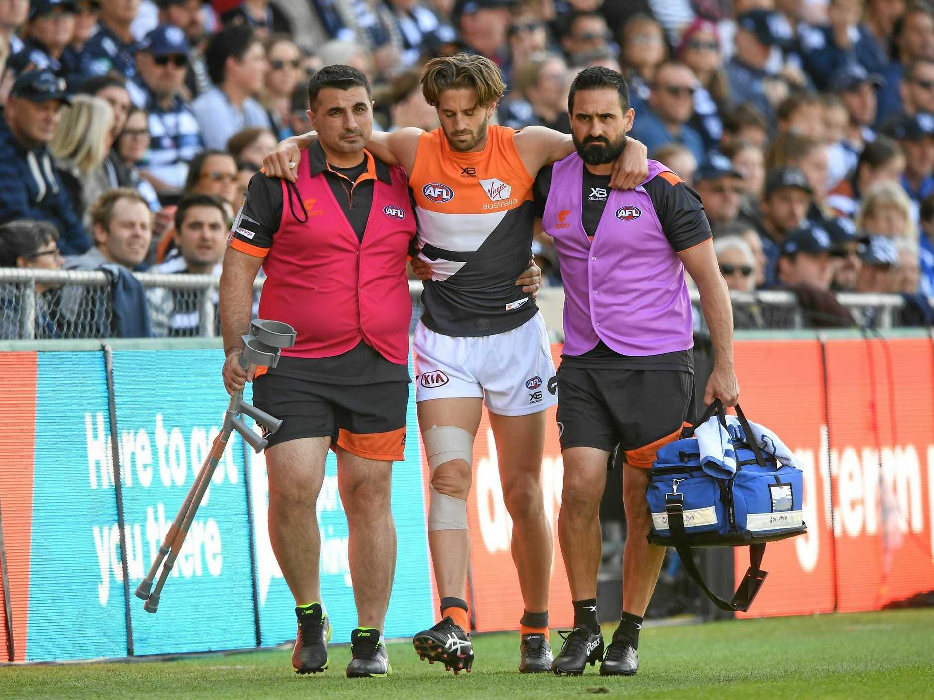 Callan Ward of the Giants is helped from the field after injuring his knee at Geelong's GMHBA Stadium on Saturday. Picture: Julian Smith/AAP