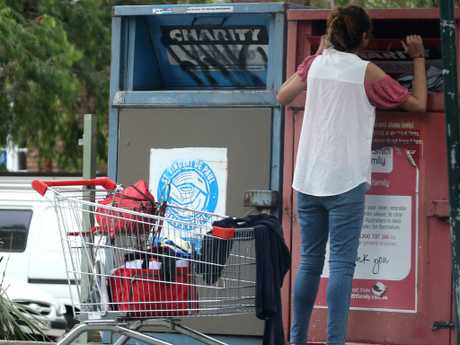 A woman goes through charity bins outside Northcott towers. Picture: John Grainger.