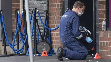 A forensic officer kneels to gather evidence at the scene of the shooting. Picture: AAP Image/Ellen SmithVING