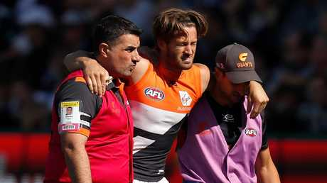 Callan Ward is helped from the ground after suffering an ACL injury on Saturday. Picture: Michael Willson/AFL Photos/Getty Images.