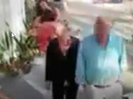 An older couple walk by as the women fall all over each other.