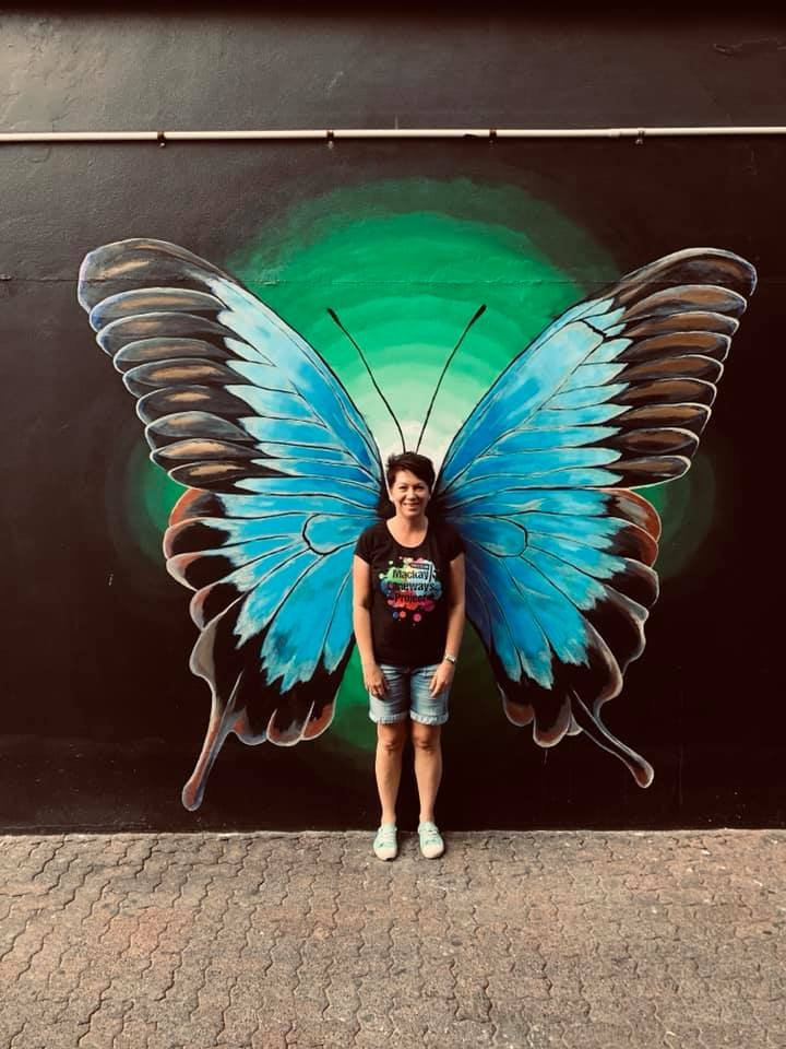 Artist Jodie Connolly and a butterfly mural in 5th Lane in the City Centre.