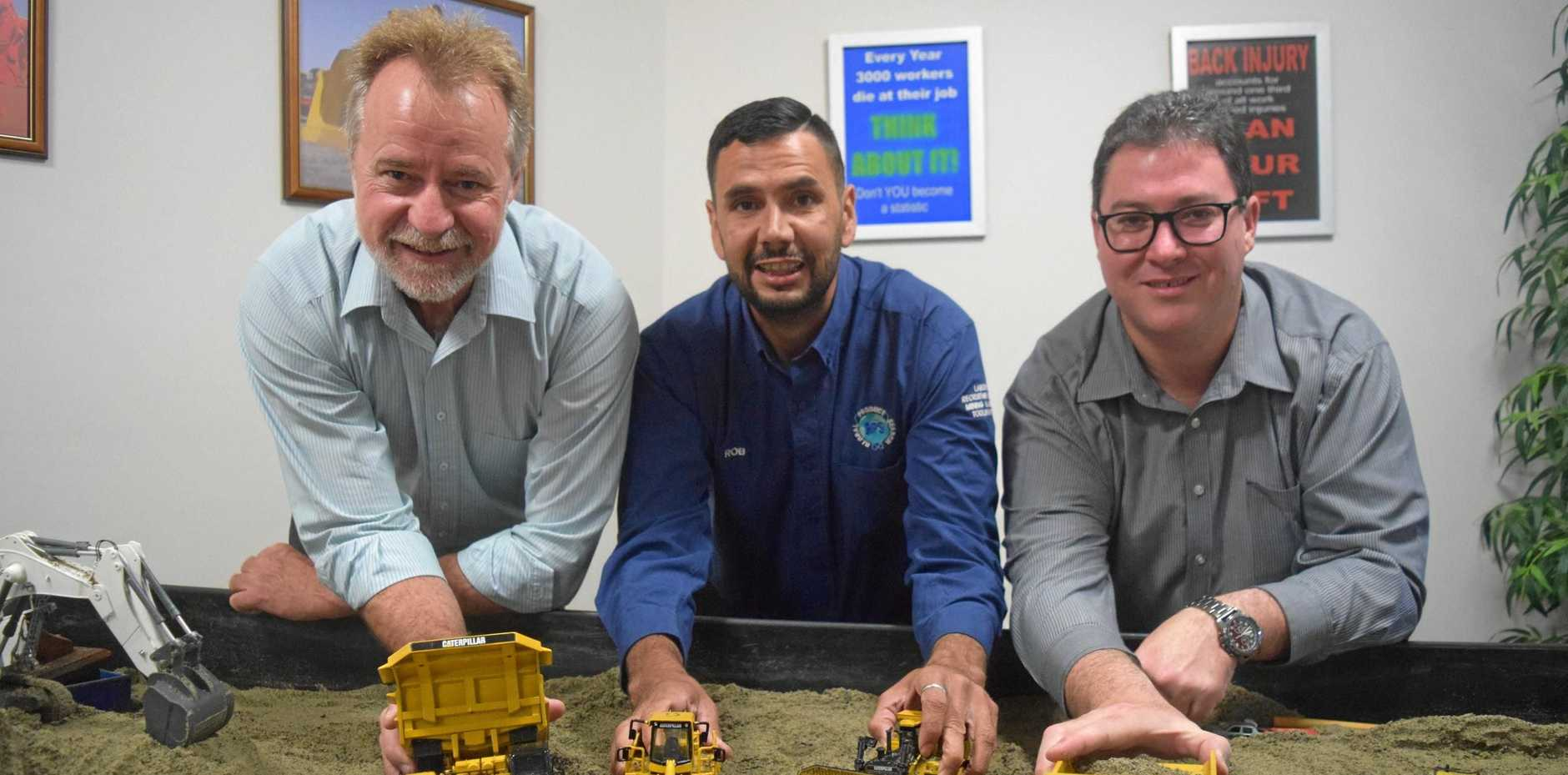 Minister for Indigenous Affairs Nigel Scullion, left, Global Product Search trainer operator Robert Gibbs and Dawson MP George Christensen thest the simulation mine site sandpit.