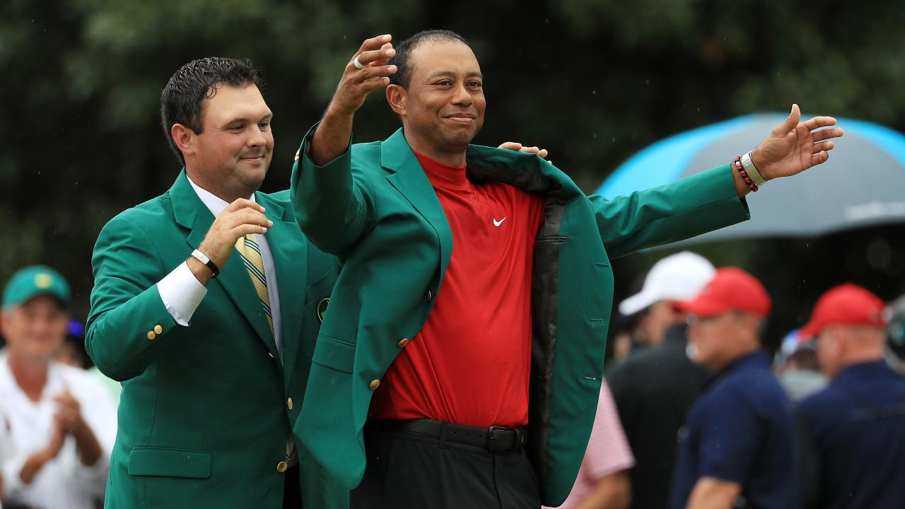 Last year's winner Patrick Reed puts the green jacket on Tiger Woods. (Photo by Mike Ehrmann/Getty Images)