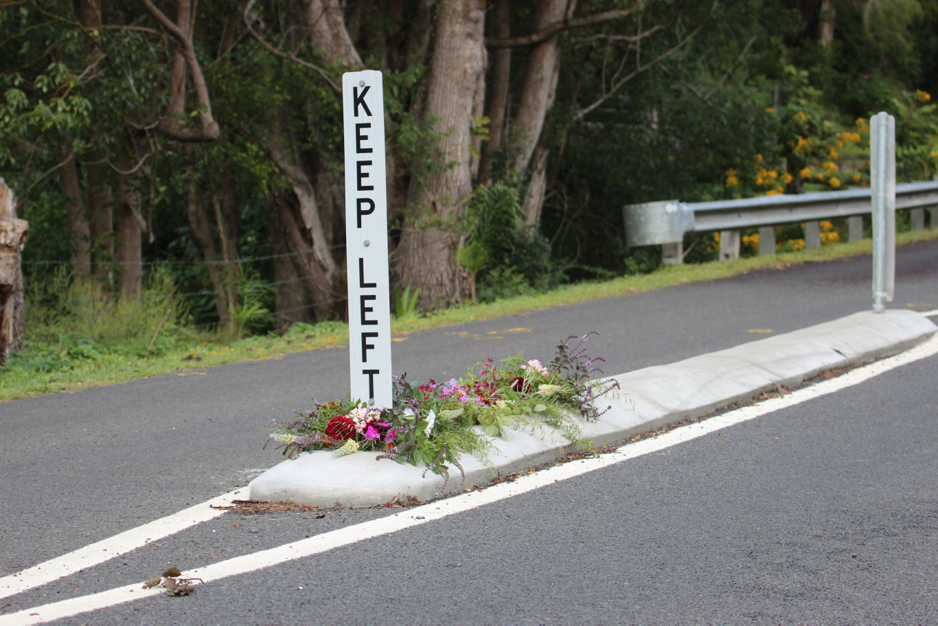 Flowers on Cecil St, Nimbin, where a pedestrian was fatally struck by a vehicle in an alleged hit-and-run incident overnight.