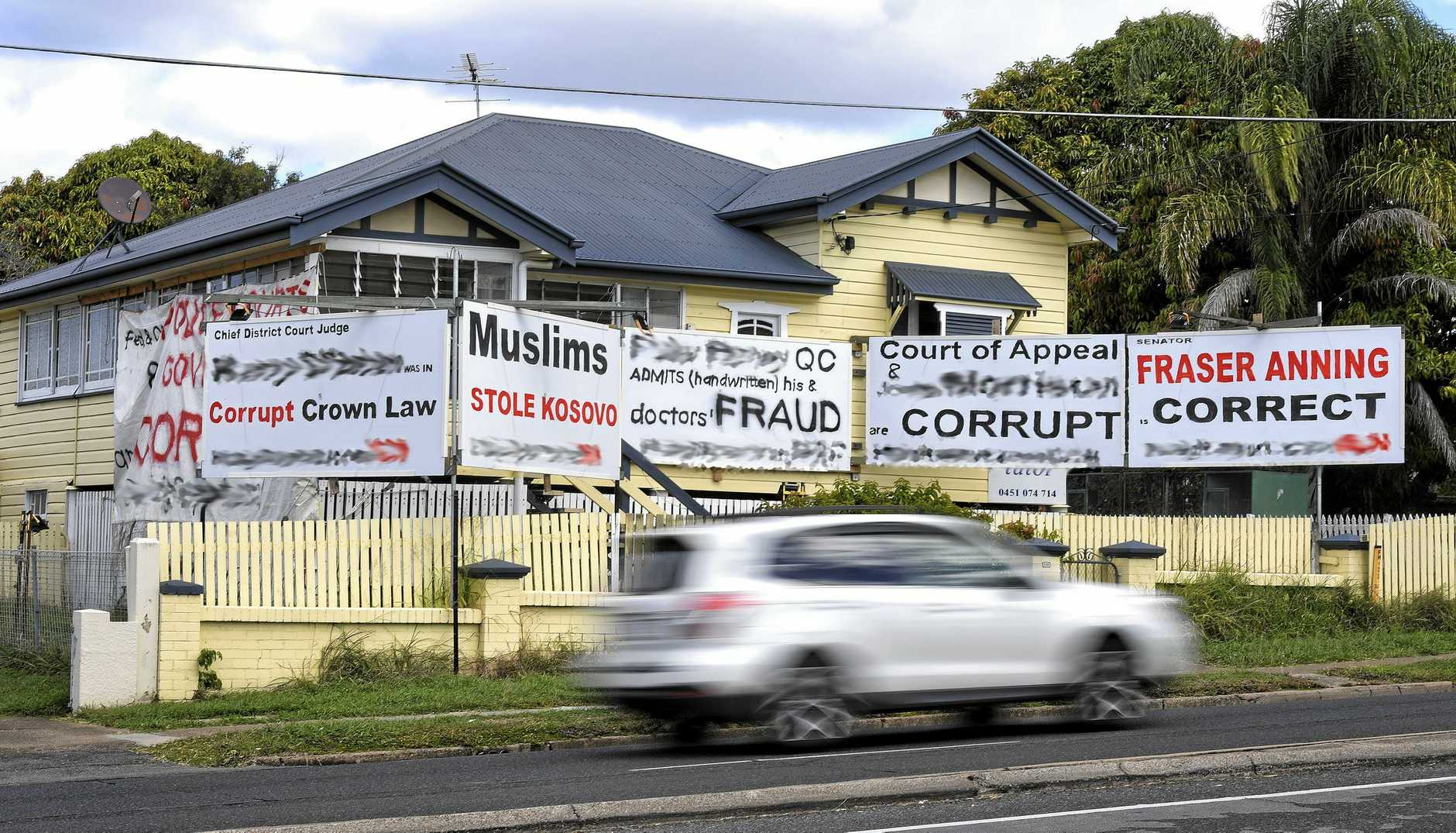 NON-COMPLIANT: Ipswich City Council has started action against a man who has built several controversial signs at the front of his Brisbane Rd home at Booval.