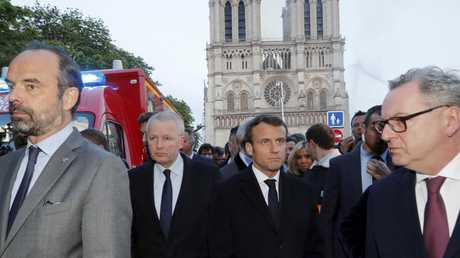French Prime Minister Edouard Philippe, left, and French President Emmanuel Macron arrive at the cathedral on Monday. Picture: Philippe Wojazer