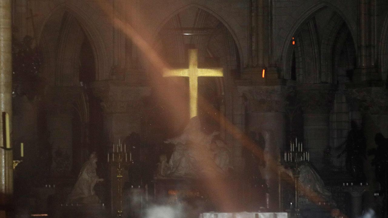 Smoke rises around the alter in front of the cross inside the Notre-Dame Cathedral. Picture: AFP