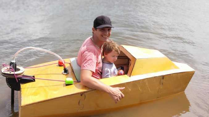 Jason Gobus and his son Franklin Gobus, 2, in his homemade boat.