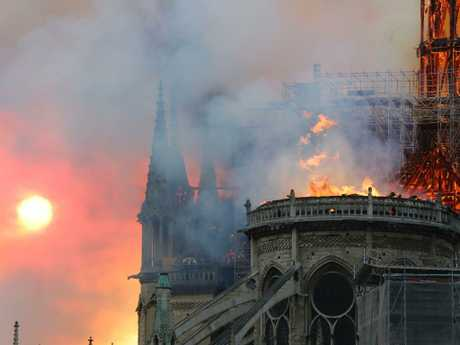 Smoke billows as flames destroy the roof of the landmark Notre-Dame Cathedral in central Paris on April 15, 2019. - A major fire broke out at the landmark Notre-Dame Cathedral in central Paris sending flames and huge clouds of grey smoke billowing into the sky, the fire service said. The flames and smoke plumed from the spire and roof of the gothic cathedral, visited by millions of people a year,