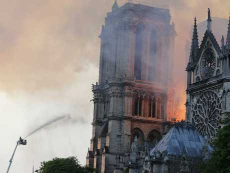 Firefighters douse flames rising from the roof at Notre-Dame Cathedral in Paris on April 15, 2019. - A fire broke out at the landmark Notre-Dame Cathedral in central Paris, potentially involving renovation works being carried out at the site, the fire service said. (Photo by Thomas SAMSON / AFP)