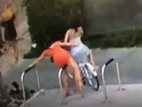 The girls were seen rubbing themselves on a set of bicycle racks on the street.