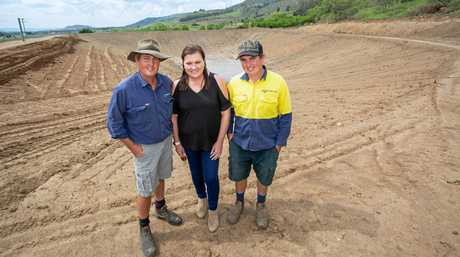Brian, Julia and Matthew Crust from Crust Farms at Mount Sylvia, in front of an on-farm dam, which will be upgraded for better water storage during drought conditions.