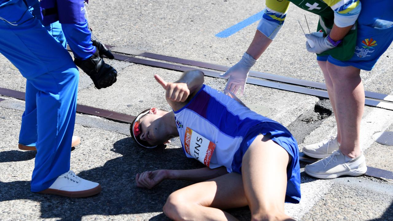 Callum Hawkins of Scotland gives the thumbs up to receive medical treatment as he collapses after being in the lead of the Men's Marathon