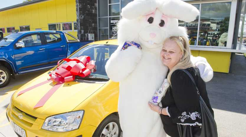 LIFE CHANGING GIFT: Cheap Cars Toowoomba manager Leslie Hollist (dressed in the rabbit costume) presents the car to Sharon Ledwidge.