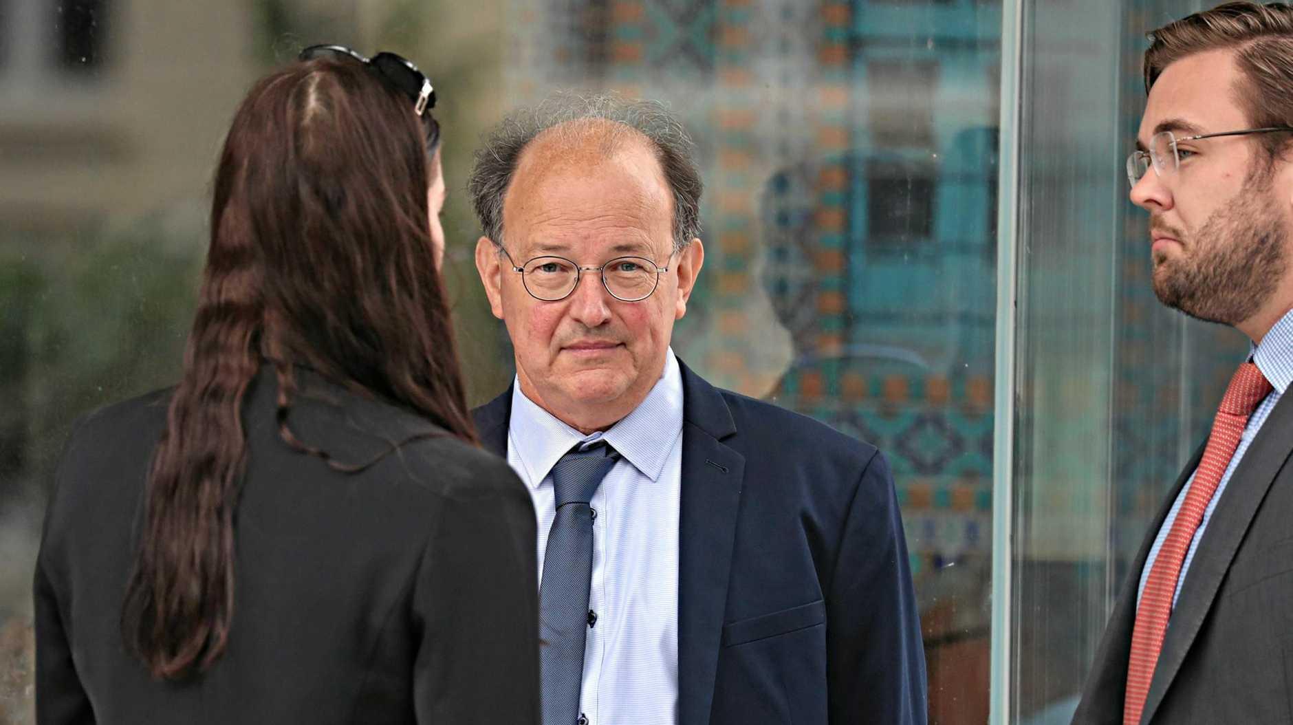Dr William Russell Massingham Pridgeon, centre, outside Brisbane Magistrates Court