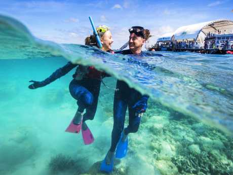 Nicola Beverley and Craig Walker from Sydney tick off a bucket list adventure after snorkelling on The Great Barrier Reef in the Whitsundays. Picture: Lachie Millard