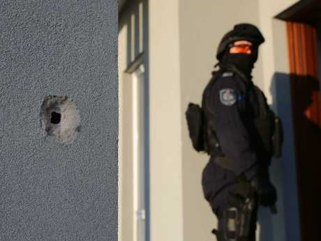 A NSW police officer stands behind a bullet hole in a wall after an attempted shooting murder in western Sydney on Tuesday. Picture: AAP Image/Supplied by NSW Police