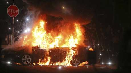 A car burns after petrol bombs were thrown at police in Creggan, Londonderry, in Northern Ireland. Picture: AP