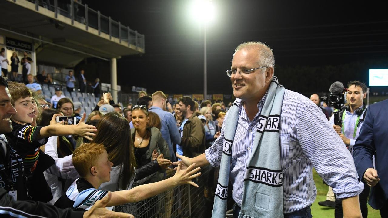Prime Minister Scott Morrison high fives the crowd as he heads to the dressing room to join the players following the Sharks win