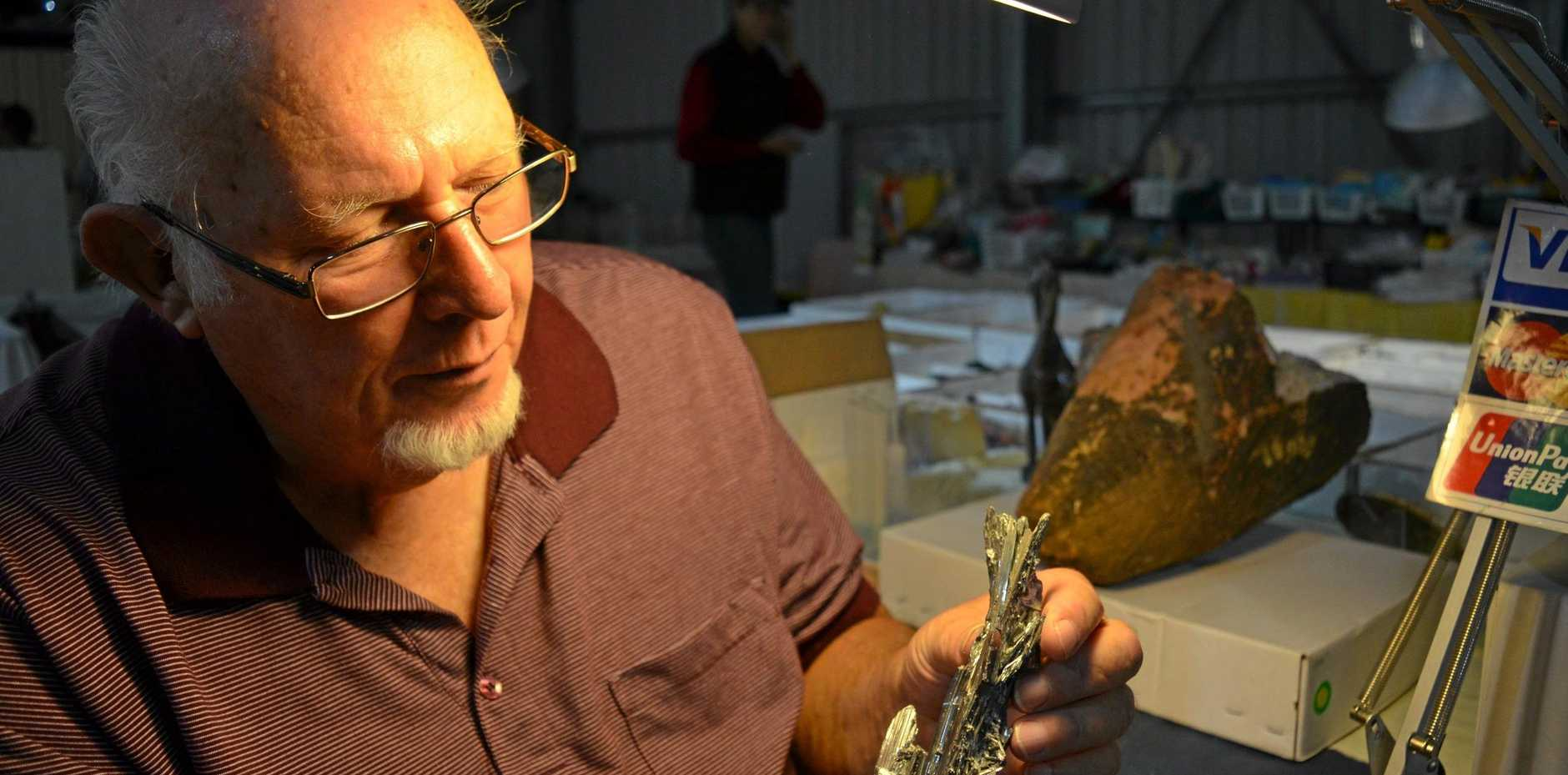 Mineral and fossil trader Peter Kettley inspects a specimen of stibnite crystal at the Warwick Rocks, Antiques, Bottles and Collectibles Fair, April 20, 2019.