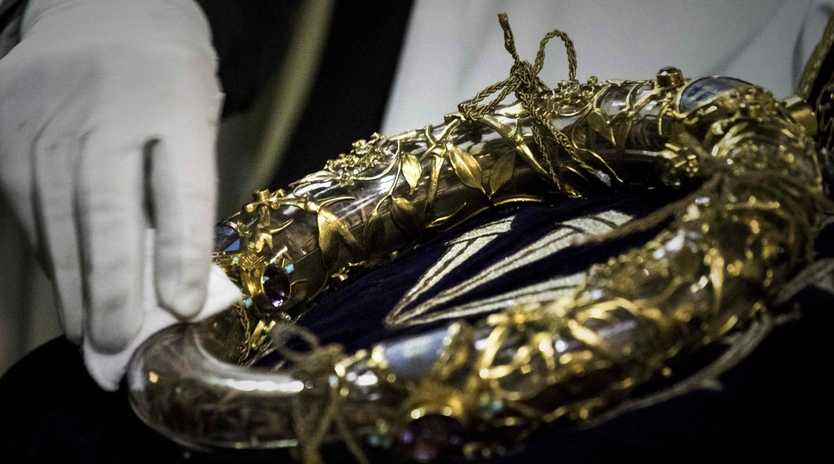 A priest wipes the Crown of Thorns, a relic of the passion of Christ- at the Notre-Dame Cathedral in Paris. Picture: Philippe Lopez